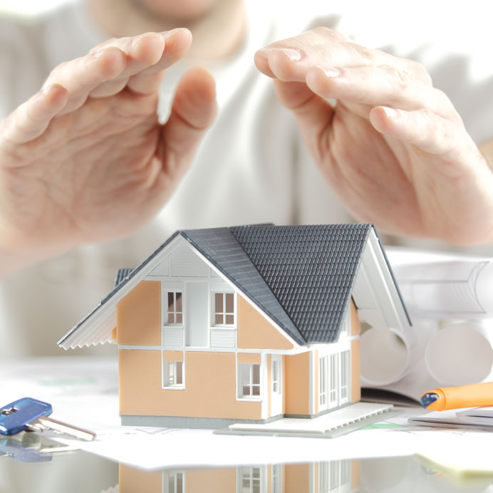 Hands covering a miniature modelk of a home as an illusion to roof coverage with insurance.
